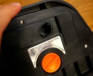 "The black circle above the tension control is one of five plastic ""posts"" that must be undone to change the palm rest."